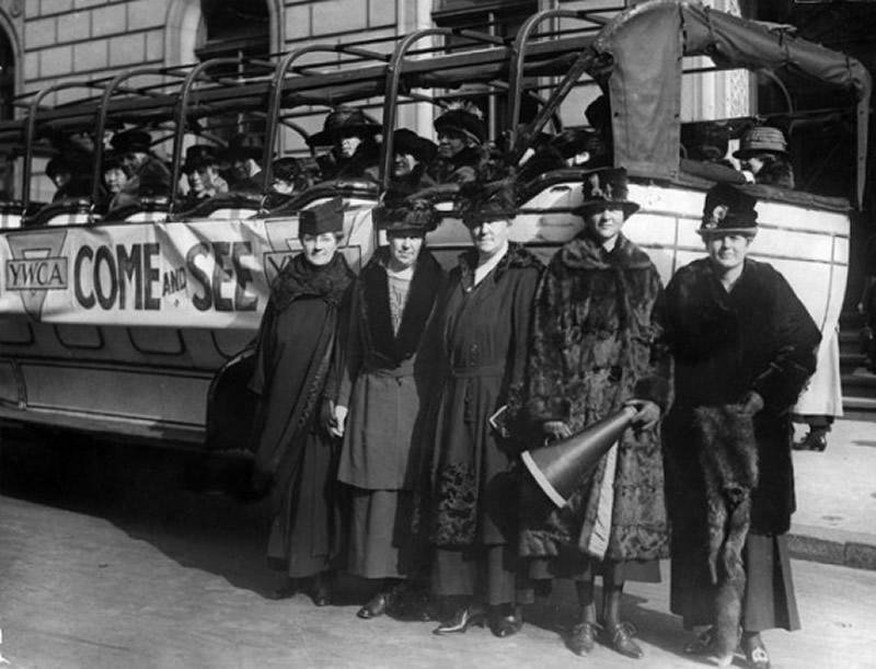 In this vintage black and white photo, 5 YWCA women advocates stand in front of a bus full of more women. A banner labeled 'YWCA Come and See' is attached to the side of the bus.