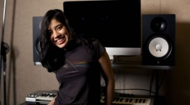 In a darkly lit room that appears to be a music room, a young smiling woman is leaning against a table that holds an electronic keyboard, a large monitor, and large speakers.