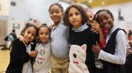 Six elementary school girls of varying height stand side-by-side as they lean on and hug each other while smiling into the camera.