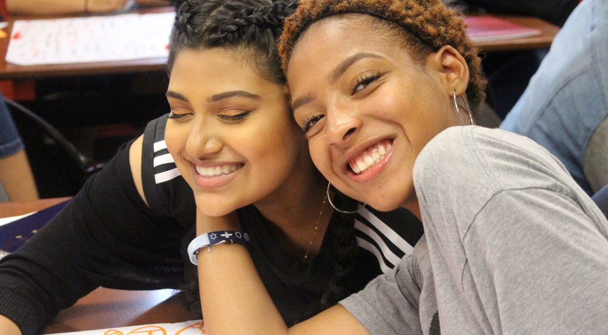 This photo is a close up of two teen women sitting at a desk and smiling into the camera with their heads against each others.
