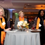 Three women stand around a small round table at a professional networking event. They all wear orange drapes across their shoulders. These women are YWCA NYC AWL 2018 Honorees Charlene Eigenberg, Beth Ann Bovino & Camille Joseph-Goldman