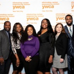In this photo, 8 people stand in a row before a white step and repeat featuring the YW orange logo. Pictured are YW Staff from left to right: YWCA NYC CEO Rosemarie Bonelli, Senior Director of Out-Of-School Time Programs Phillip Colas, Program Director Ewuraesi Dadzie, Program Director Janet Cooper, Program Director Karlene James, Benefits Administrator Nicole Doherty, Program Director Christopher Anderson