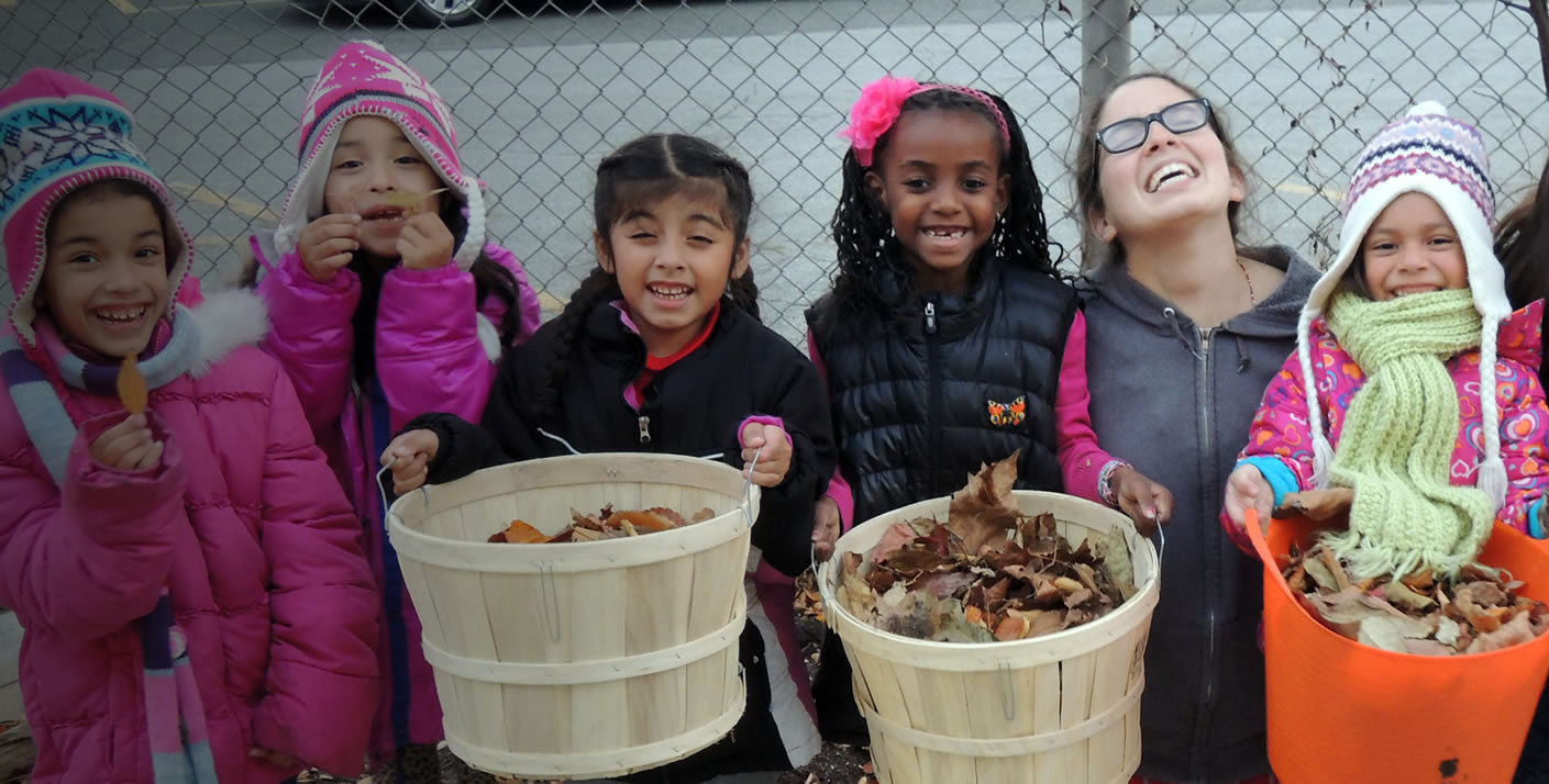 Six elementary school girls carrying baskets of autumn leaves make silly faces into the camera.