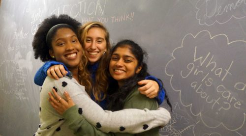 Three teenaged women embrace while smiling into the camera. Girl empowerment notes are written on the chalkboard wall behind them.