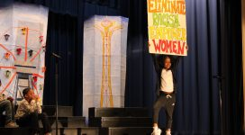 PS 9o students take a Stand Against Racism at the annual event. In this photo an elementary school girl poses on stage holding a sign that reads Eliminate Racism. Empower Women.