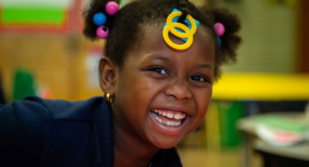 Young girl from our Out of School Time Program smiles brightly into the camera while sitting in a classroom.